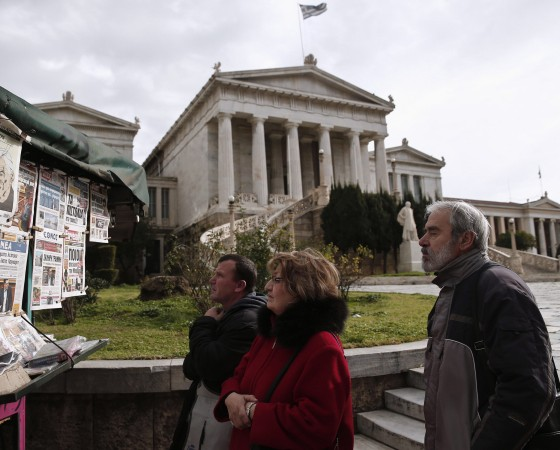 People read newspaper headlines in front of the National Library in Athens