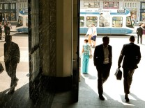 People walk through the entrance of the headquarters of Swiss bank Credit Suisse in Zurich