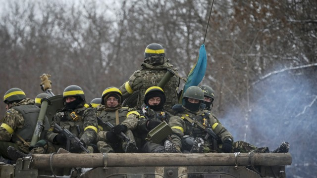 Members of the Ukrainian armed forces ride on an armoured personnel carrier (APC) near Debaltseve