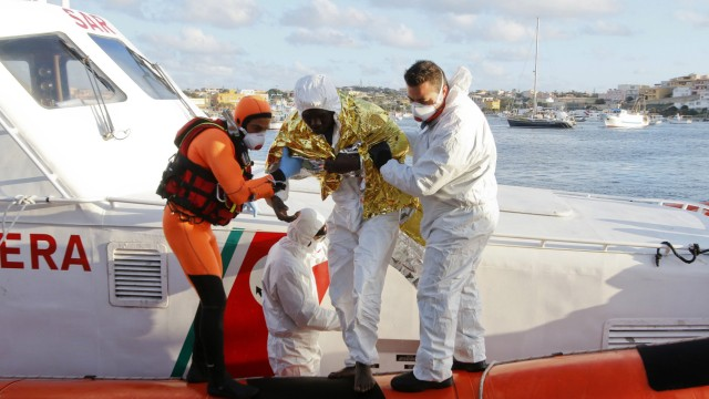 A migrant who survived a shipwreck is helped as he arrives with others at the Lampedusa harbour