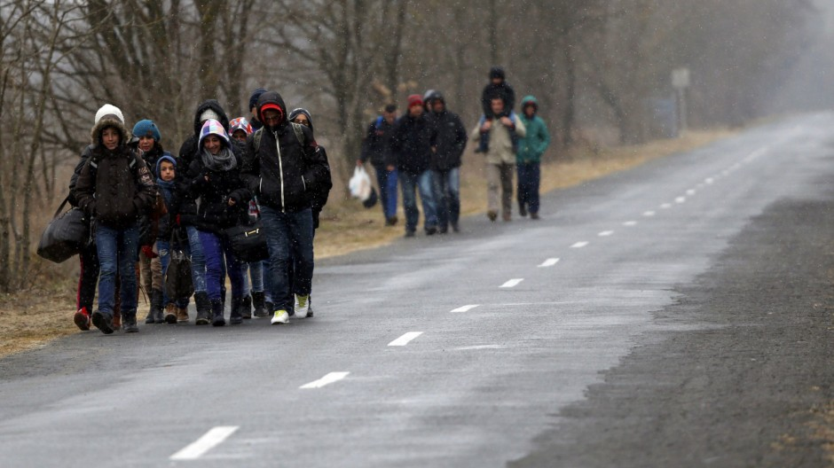 A group of Kosovars walk along a road after they crossed illegally the Hungarian-Serbian border near the village of Asotthalom