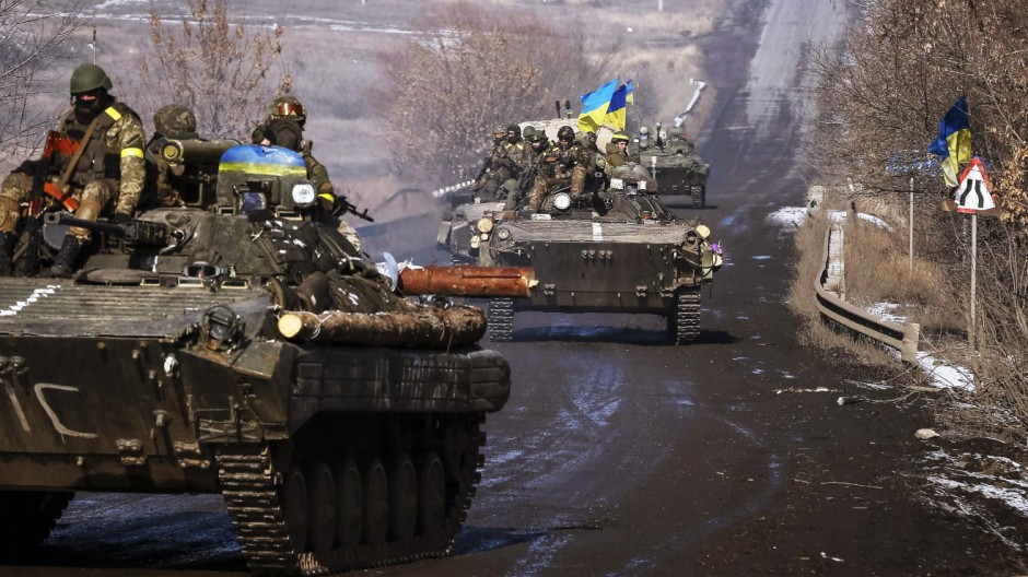 Members of the Ukrainian armed forces ride on armoured personnel carriers near Debaltseve