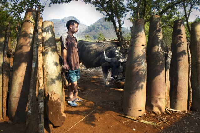 Phue Ya stands in the gate of his cluster bomb casing fence