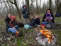 A Kosovar family warms up around an open fire after they crossed illegally the Hungarian-Serbian border near the village of Asotthalom