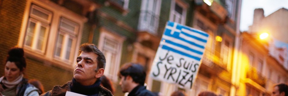 A man holds a placard during a vigil to support the newly elected Greek government