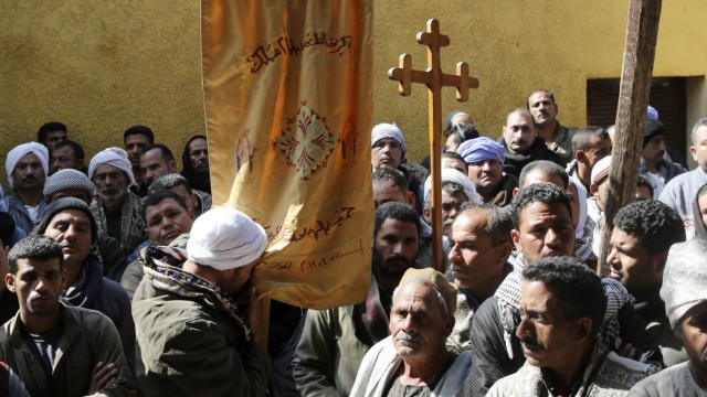 A Coptic man kisses a prayer banner before a mass at a church in the south of Cairo for the Egyptian Coptic men who were killed in Libya