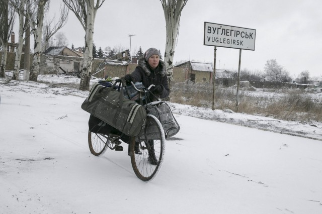 Local woman pushes her bicycle near a sign to the town of Vuhlehirsk, west of Debaltseve