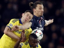 Paris St Germain's Ibrahimovic challenges Chelsea's Ivanovic and Ramires during their Champions League round of 16 first leg soccer match at the Parc des Princes Stadium in Paris