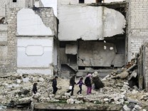 Children walk on the debris of a damaged building at al-Myassar neighborhood of Aleppo