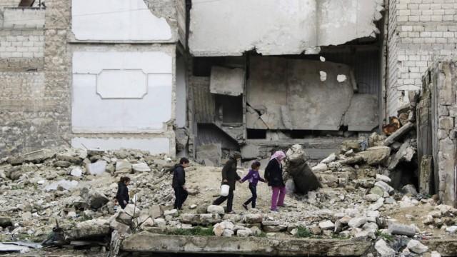 Children walk on the debris of a damaged building at al-Myassar neighborhood of Aleppo
