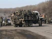 Ukrainian servicemen ride on a military vehicle as they leave area around Debaltseve