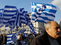 Greek national flags displayed for sale flutter during an anti-austerity pro-government demonstration in front of the parliament in Athens
