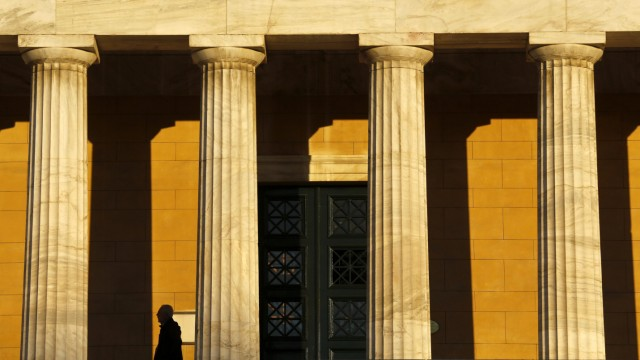 A man is silhouetted as he makes his way under the peristyle of the Greek parliament building during a demonstration in Athens