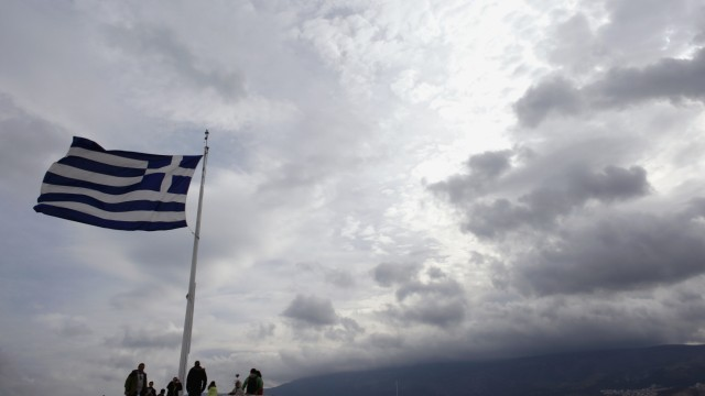 Tourists stand under a Greek national flag atop Acropolis hill in Athens