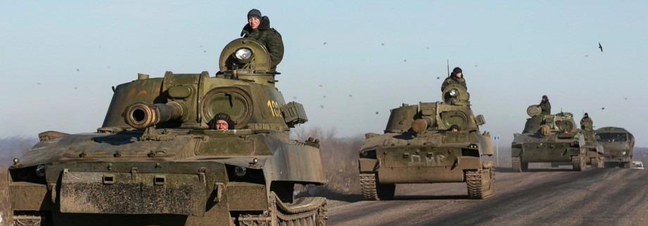 Soldiers of the separatist self-proclaimed Donetsk People's Republic army ride in mobile artillery cannons as they are pulling back from from Debaltseve
