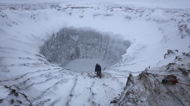 A member of an expedition group stands on the edge of a newly formed crater on the Yamal Peninsula, northern Siberia