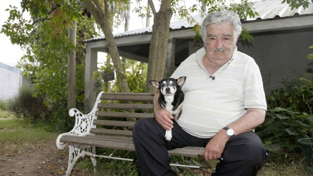 Uruguay's President Mujica pose for picture with dog Manuela after interview with Reuters in farm in outskirts of Montevideo