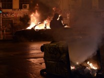 People walk past a burning car, set on fire by youths at the end of a demonstration, in the Exarchia district of Athens,on February 26, 2015. Several hundred people protested in Athens against a compr