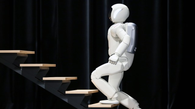 Honda's latest version of the Asimo humanoid robot walks up stairs during a presentation in Zaventem near Brussels
