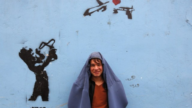 A male Afghan women's rights activist poses for pictures in burqa to show solidarity to Afghan women ahead of International Women's Day in Kabul