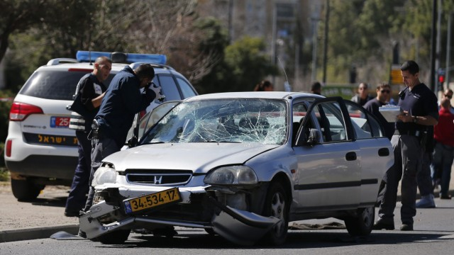 Israeli policemen inspect the car used by a Palestinian motorist to ram into a group of pedestrians in Jerusalem
