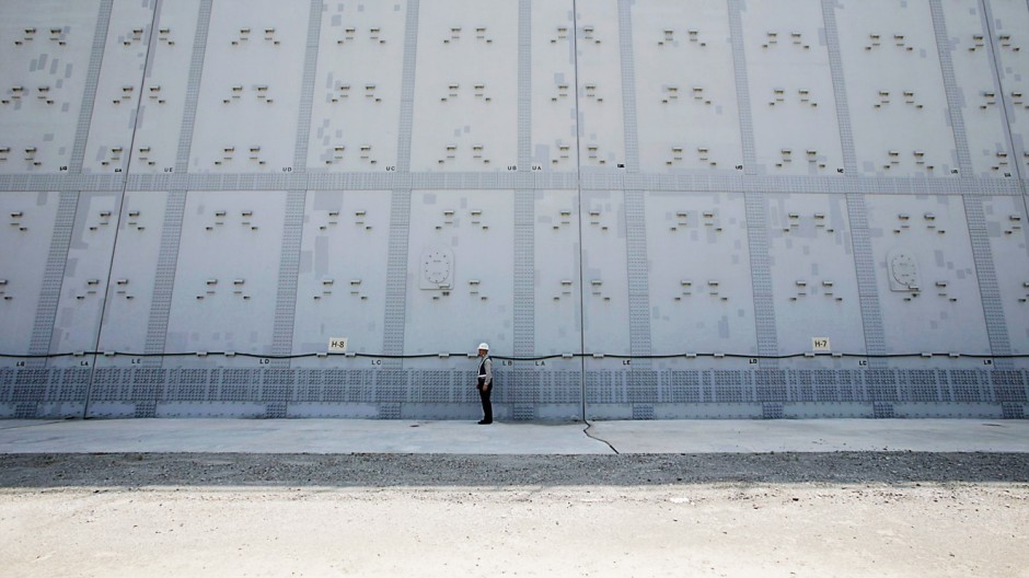 File photo shows a worker standing in front of a tsunami defence wall at Chubu Electric Power Co.'s Hamaoka Nuclear Power Station in Omaezaki