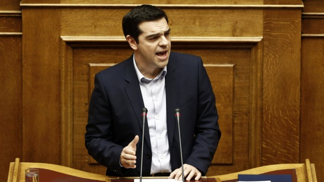 Greek PM Tsipras addresses lawmakers during a parliamentary session for the creation of a committee for claiming World War II war reparations at the parliament building in Athens