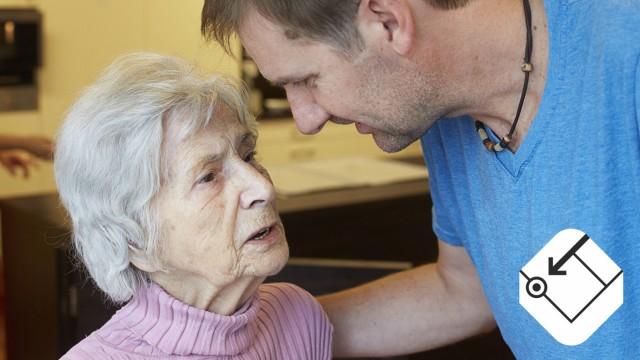 Geriatric nurse talking to age demented senior woman in a nursing home model released Symbolfoto pro