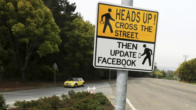 A sign is shown at a crosswalk near California State University in Hayward, California