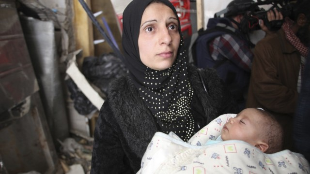A woman holds a baby at the Yarmouk refugee camp