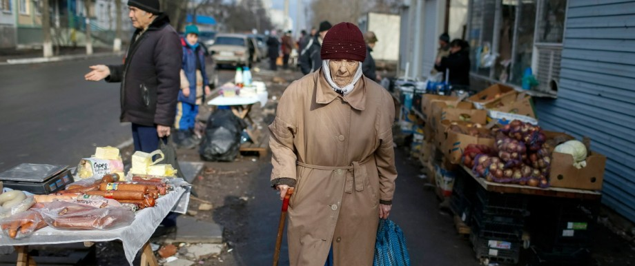 A woman walks past street vendors at a residential sector affected by shelling in Mariupol, a city on the Sea of Azov, eastern Ukraine