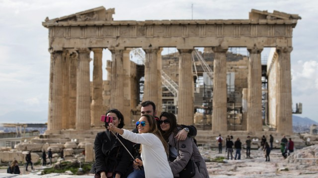 Tourists take a selfie photograph of themselves in front of the Parthenon Temple, at the archaeological site of the Acropolis Hill in Athens