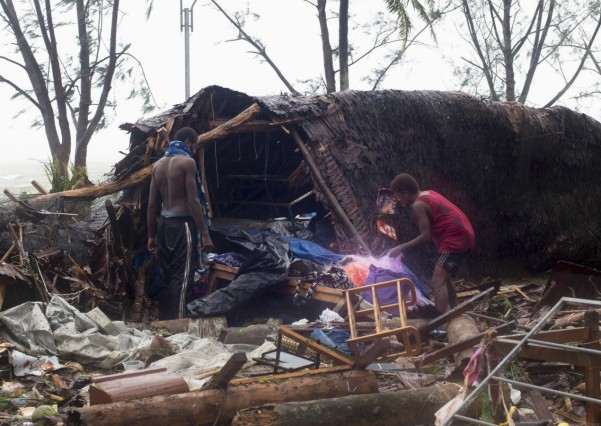 Local residents look through the remains of a small shelter in Port Vila, the capital city of the Pacific island nation of Vanuatu
