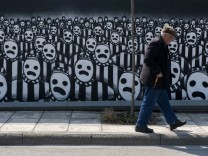 A man walks past a graffiti dedicated to the Holocaust in the northern port city of Thessaloniki