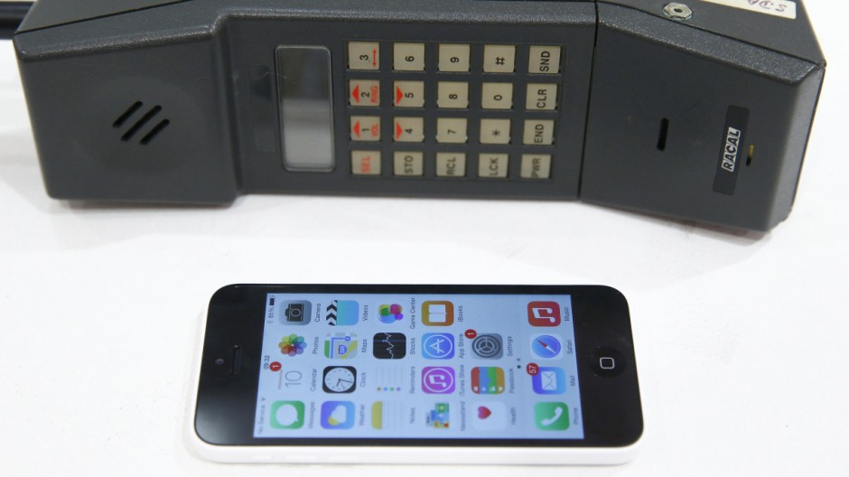 A photo-illustration shows an iPhone 5 next to a vintage mobile phone sold by Vodafone in Vodafone's Oxford Street store during an event to mark the 30th anniversary of the first mobile phone call in the UK, in central London