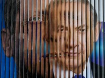 Israel's Prime Minister Netanyahu and Herzog are pictured together on a rotating billboard in Tel Aviv