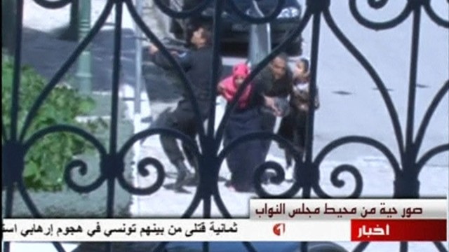 A still image taken from video shows tourists running for cover as an armed man stands guard at Tunisia's national museum in Tunis