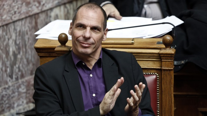 Greek Finance Minister Varoufakis applauds during a parliamentary session in Athens