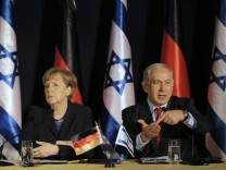 Israel's Prime Minister Netanyahu sits next to German Chancellor Merkel during their joint news conference in Jerusalem