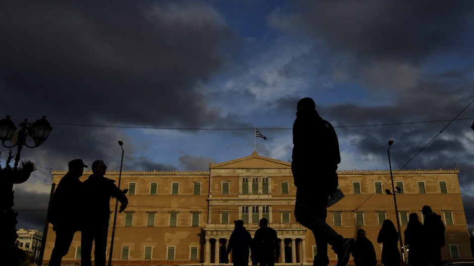 People walks in front of the Greek Parliament building in Athens