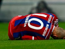 Munich's Robben lies injured on the pitch during their Bundesliga first division soccer match against Borussia Moenchengladbach in Munich