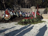 Shadows of people are seen near an unnamed grave, believed to be that of ousted Ukrainian president Viktor Yanukovich's son Viktor, at the Brotherhood cemetery in Sevastopol