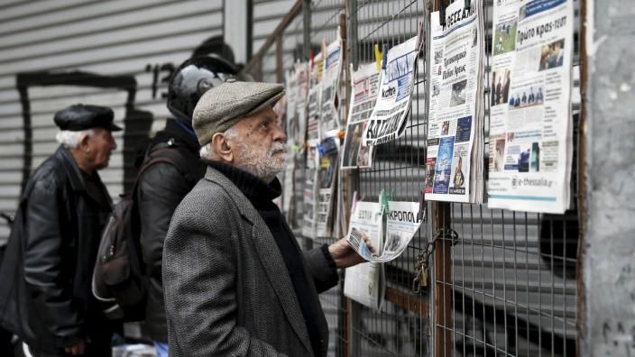 People read newspaper headlines in Athens