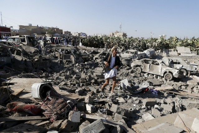 An armed man walks on the rubble of houses destroyed by an air strike near Sanaa Airport
