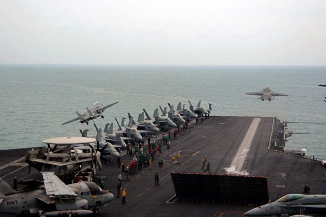 Pair of F-14D Tomcats launched simultaneously from bow and waist steam-powered catapults on flight deck of Nimitz-class aircraft carrier USS Theodore Roosevelt