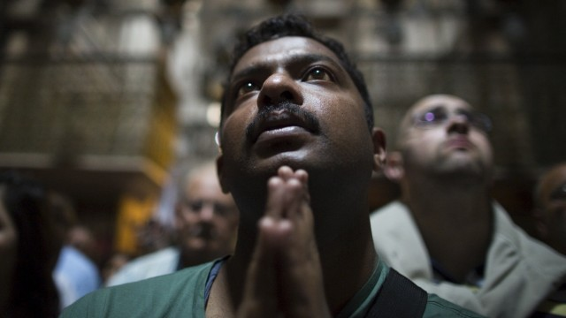 A Christian worshipper take part in a prayer after a procession in the Church of the Holy Sepulchre on Good Friday, during Holy Week in Jerusalem's Old City