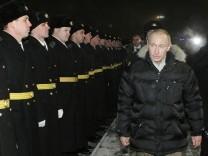 Russia's Prime Minister Putin walks past seamen as he visits Sevmash shipyard in Severodvinsk