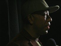 Record mogul Russell Simmons speaks to a reporter before the Baby Phat 2007 Fall collection during New York Fashion Week; Russell Simmons