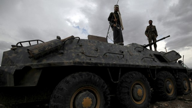 Plain-clothes policemen stand on top of a police vehicle at a checkpoint in Sanaa