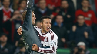 Munich's Thiago celebrates with goalkeeper Neuer after scoring the decisive penalty to defeat Bayer Leverkusen in their quarter-final German Cup (DFB-Pokal) soccer match in Leverkusen